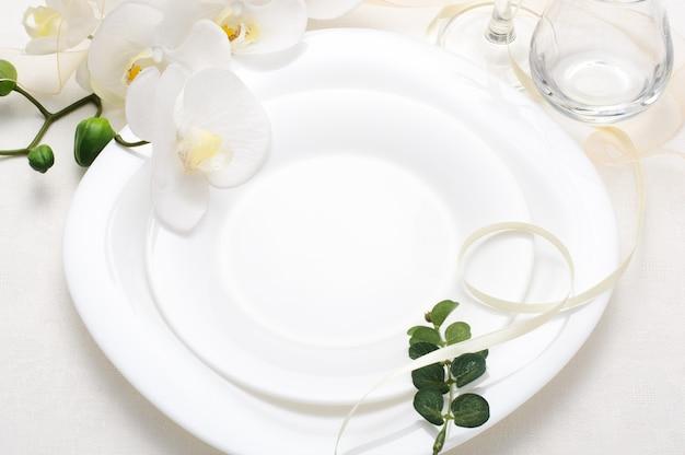 난초, 흰색 빈 접시와 흰색 배경에 실크 리본 휴일 로맨틱 테이블 설정, 웨딩 테이블 설정