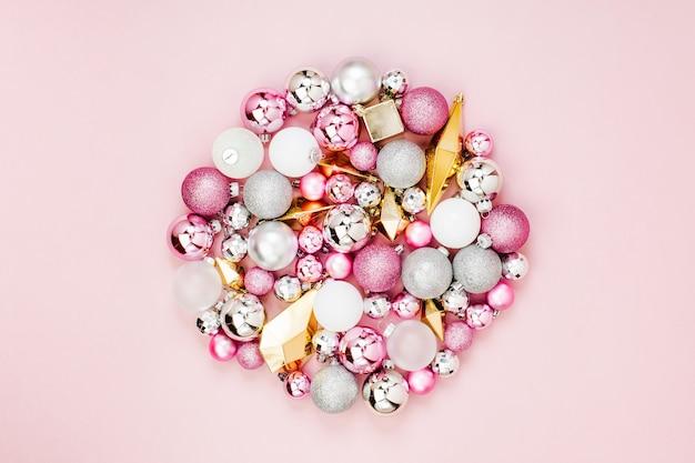 Праздничная круглая композиция со стильными рождественскими блестящими шарами и золотыми кристаллами на пастельно-розовом фоне. плоская планировка, вид сверху