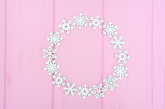 Holiday round frame made of christmas white snowflakes on pink wooden