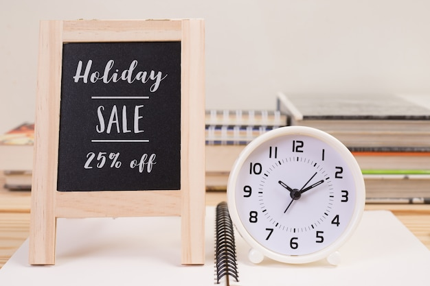 Holiday sale 25 percent off banner with clock on table