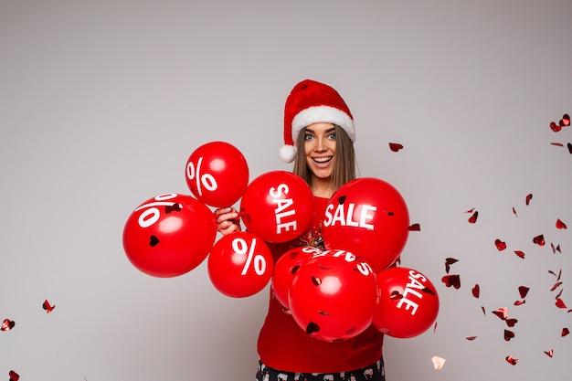 Праздничная распродажа и скидка, красивая девушка в красной шляпе с воздушными шарами на сером