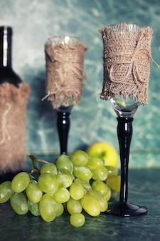 背景に緑のブドウと休日のセットワインボトル