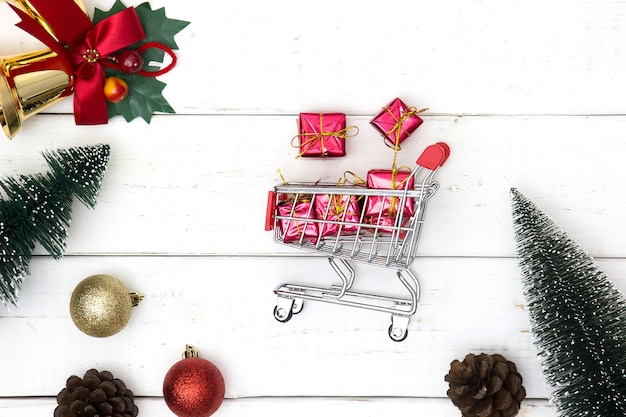 Holiday shopping and christmas gift exchange concept with shopping cart and xmas decorations on wooden white background. flat lay.