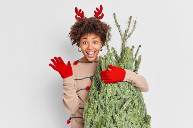 Concetto di shopping natalizio. la donna etnica positiva indossa le corna di renna rossa e le onde dei guanti mano nel gesto di ciao sceglie l'albero di chrirtmas al mercato di strada per la decorazione a casa. buon anno