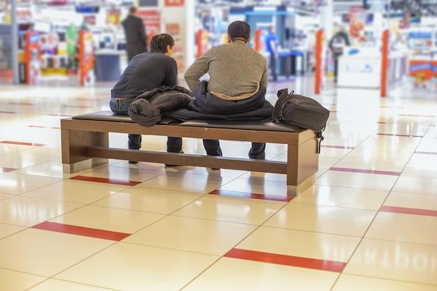 女性のコンセプトを持つホリデーショッピングの男性2人の疲れた男性がショッピングセンターのベンチに座っています