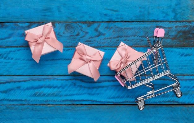 Праздничный шоппинг. тележка супермаркета с подарочными коробками на голубой деревянной поверхности. вид сверху