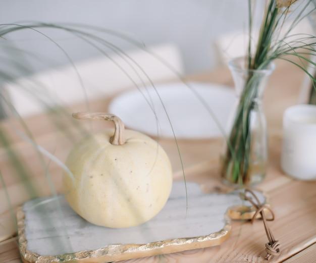 Украшение праздничного стола белыми декоративными тыквенными тарелками и свечами на деревянном фоне