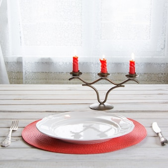 Holiday table place setting with white dishware and red candles.