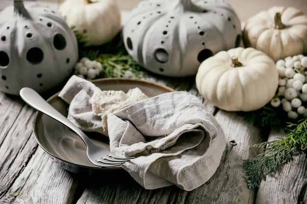 Украшение праздничного стола с белыми декоративными тыквами, глиняные тыквы, ветки туи, пустая тарелка с тканевой салфеткой, столовые приборы над старым деревянным столом. закрыть вверх