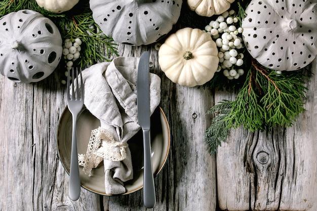 Украшение праздничного стола с белыми декоративными тыквами, глиняные тыквы, ветки туи, пустая тарелка с тканевой салфеткой, столовые приборы над старым деревянным столом. плоская планировка, простор
