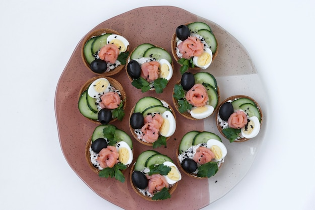흰색 배경에 있는 접시에 치즈, 연어, 블랙 올리브, 메추라기 알, 오이가 있는 휴일 타르트, 상위 뷰, 근접 촬영