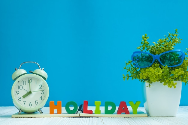 Holiday text, notebook paper, alarm clock and little tree on wood