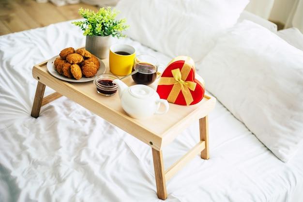 Праздничные вещи в спальне. большая красная подарочная коробка в форме сердца на кровати. счастливое утро подарки.