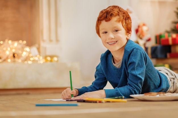 Holiday time. joyful redhead boy with a cheerful smile on his face while lying on the floor and drawing with colorful pencils.