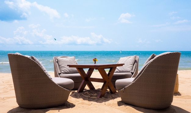 Holiday time with a relaxing chair, furniture living set on the beach by the summer sea at pattaya, thailand