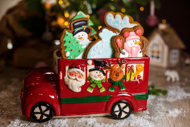 Holiday traditional food bakery. decorative toy car with christmas gingerbread cakes in cozy warm decoration with garland lights
