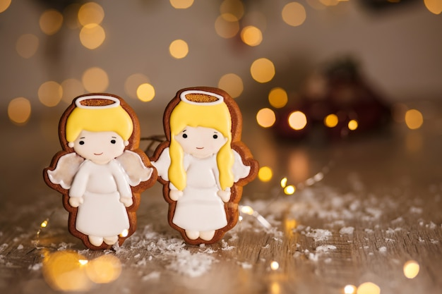 Holiday traditional food bakery. gingerbread pair of little cute angels boy and girl in cozy warm decoration with garland lights