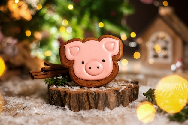 Holiday traditional food bakery. gingerbread pink pig head in cozy warm decoration with garland lights