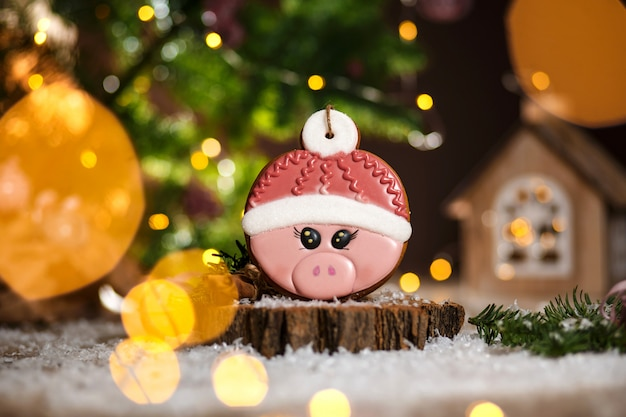 Holiday traditional food bakery. gingerbread pink pig head in hat in cozy warm decoration with garland lights