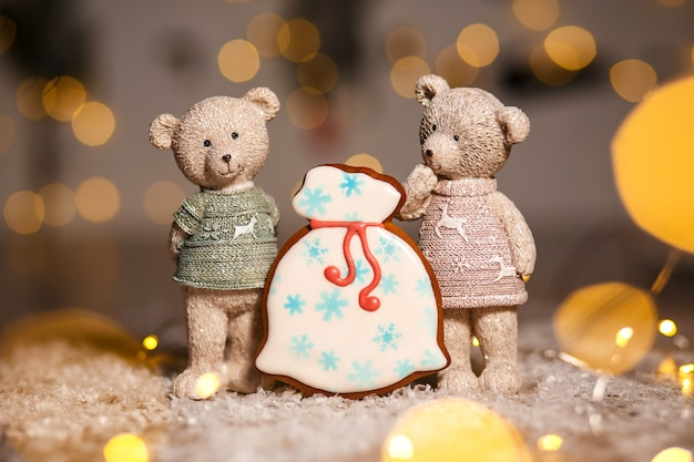 Holiday traditional food bakery, gingerbread santa's bag of gifts and two decorative bears in cozy warm decoration with garland lights