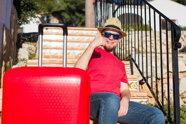 休日、旅行、観光の概念-階段に座って親指を立てて赤いスーツケースを持つハンサムな男