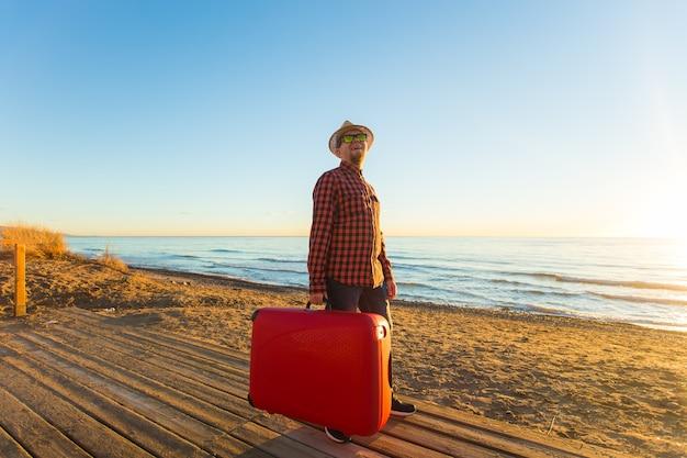 休日、旅行、観光のコンセプト-砂浜の上のスーツケースを持つハンサムな男。