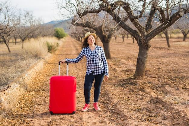 休日、旅行、観光のコンセプト。夏の自然に赤いスーツケースを持つ若い女性。