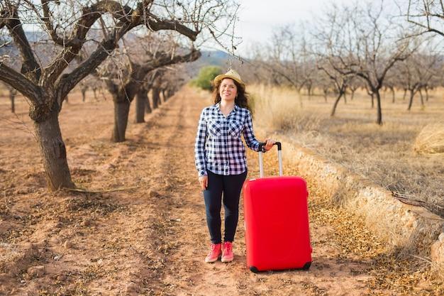 휴일, 여행 및 관광 개념입니다. 여름 자연에 빨간 가방을 가진 젊은 여자.