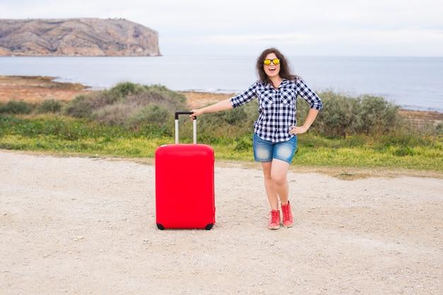 休日、旅行、観光の概念-海の背景に赤いスーツケースを持つ若い女性