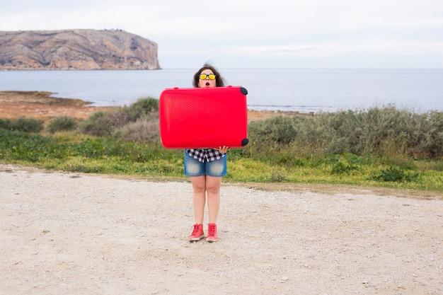 休日、旅行、観光のコンセプト。海の背景に赤いスーツケースを持つ若い女性。