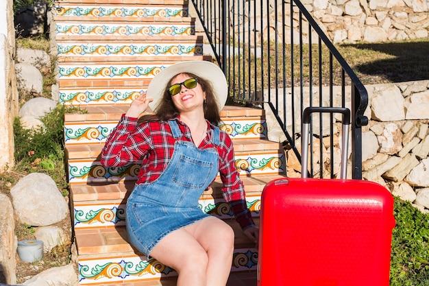 휴일, 여행 및 관광 개념입니다. 계단에 앉아 빨간 가방으로 아름 다운 젊은 여자.