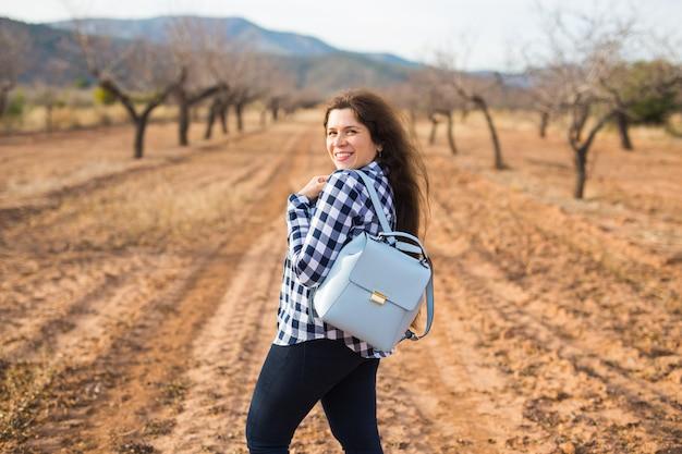 休日、旅行、観光のコンセプト-夏の自然にスタイリッシュなバックパックを持つ若い女性。