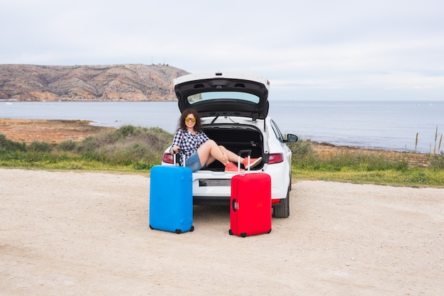 休日、旅行、観光のコンセプト-車の旅でスーツケースを持った若い女性。