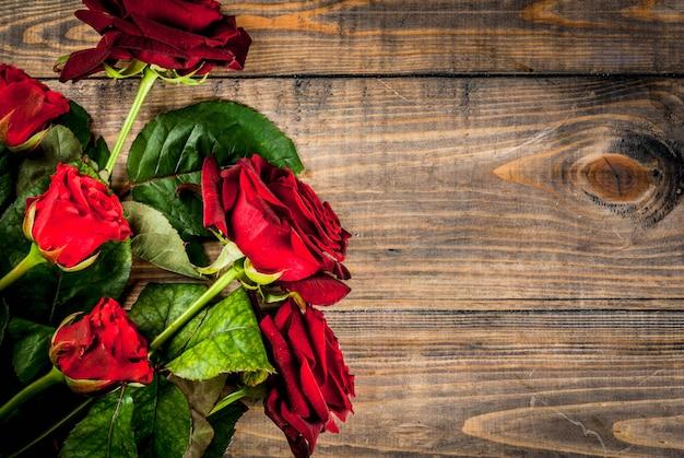 休日、バレンタインデー。赤いバラの花束、赤いリボンとネクタイ。木製のテーブル、トップビューcopyspace