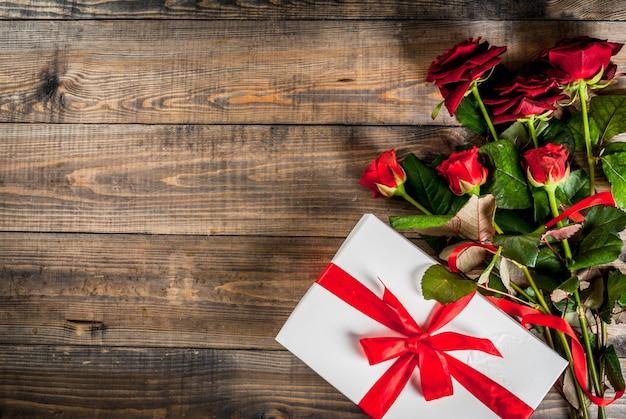 休日、バレンタインデー。赤いバラの花束、赤いリボンとネクタイ、ラップされたギフトボックス。木製のテーブル、トップビュー