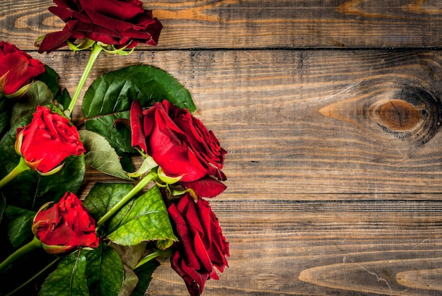 Holiday  , valentine's day. bouquet of red roses, tie with a red ribbon. on a wooden table, top view copyspace
