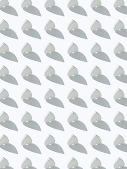 Праздничный узор из перевернутых сердечек из гипса на светло-серой стене с жесткими тенями.