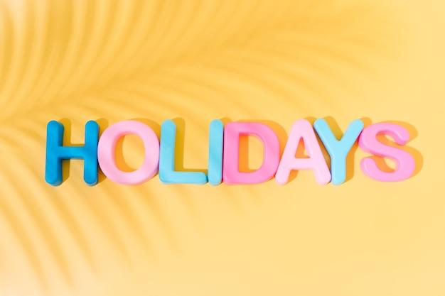 Праздничное слово в цветах с тенью пальмовых листьев на желтом фоне летней концепции копией пространства