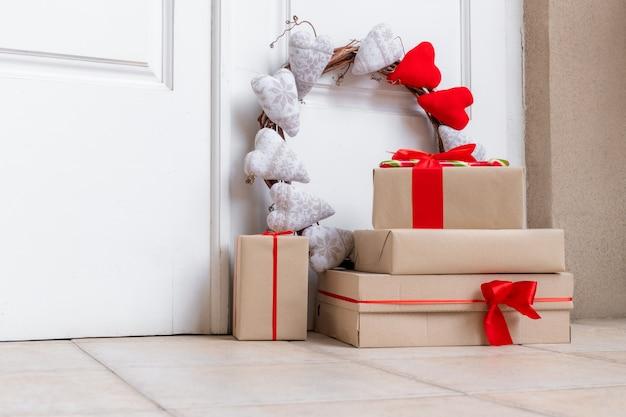 Праздничный венок с сердечками и коробками для покупок на полу возле белой двери