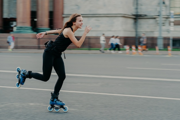Holidays and active lifestyle concept. slim healthy european woman rollerskates on high speed