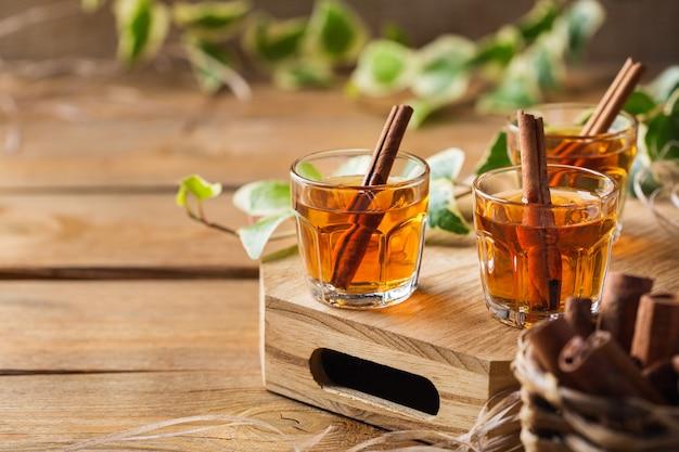休日、アルコール飲料、飲み物、食後酒の概念。木製のテーブルに強いアルコールとシナモンスティックで撮影