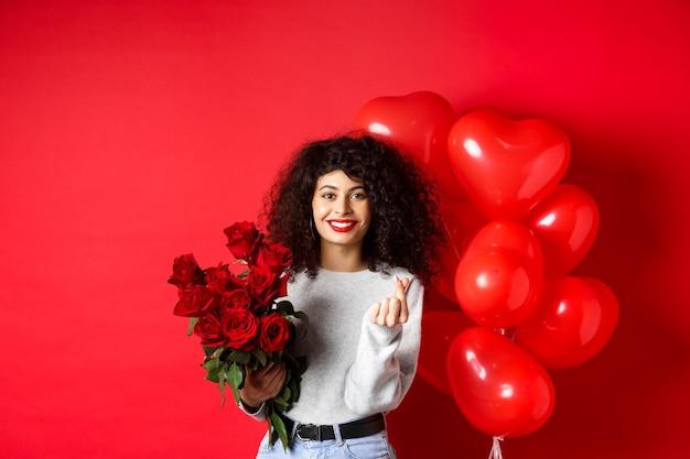 휴일 및 축하. 아름다운 여자 친구는 기념일에 꽃을 받아 손가락 마음을 보여주고 파티 풍선, 빨간색 배경 근처에 서 있습니다.