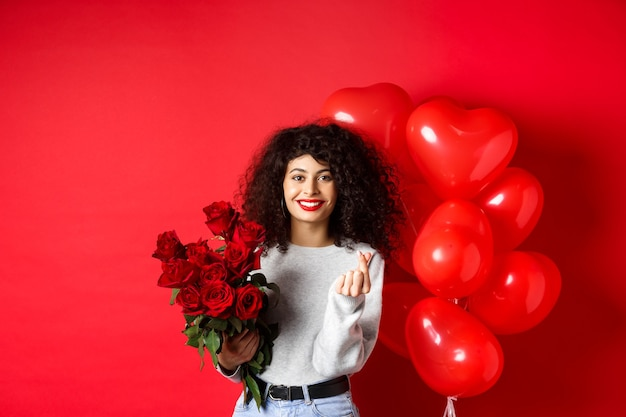 휴일 및 축하. 아름다운 여자 친구는 기념일에 꽃을 받고 손가락 마음을 보여주고 파티 풍선, 붉은 벽 근처에 서 있습니다.
