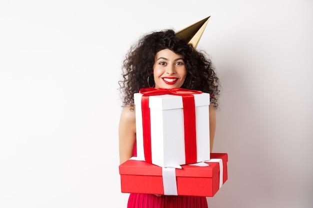 休日とお祝い。巻き毛、パーティーハットをかぶって、大きなプレゼントを持って、幸せな笑顔、誕生日プレゼントを受け取り、白い背景の上に立っている美しい女性。