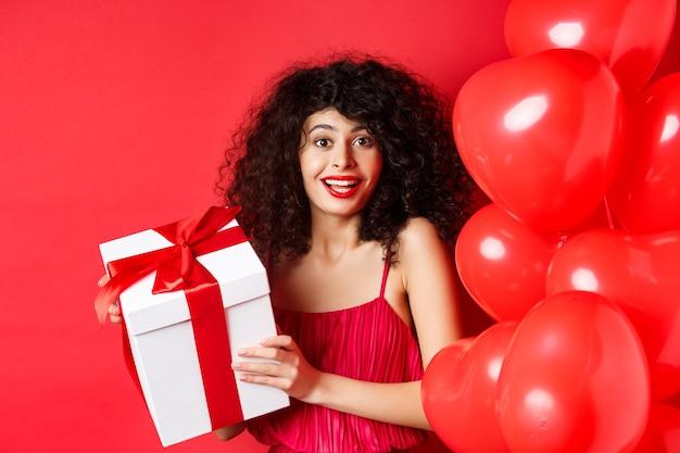 휴일 및 축하. 곱슬 머리, 심장 풍선 근처에 서, 선물 상자를 들고 웃 고 행복, 흰색 배경 가진 아름 다운 여자.