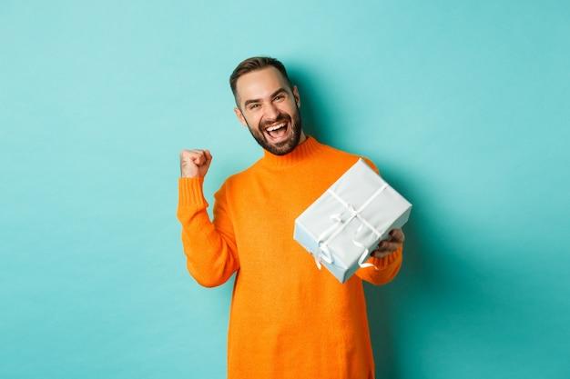 Праздники и концепция празднования. возбужденный мужчина получает подарок, в настоящее время выглядит счастливым и улыбается, стоя на синем фоне.