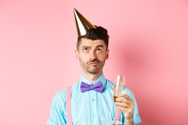 休日とお祝いのコンセプト。誕生日パーティーの帽子をかぶって、シャンパンのグラスを持って、懐疑的な顔で見上げて、ピンクの背景の上に立っている不機嫌そうな男。
