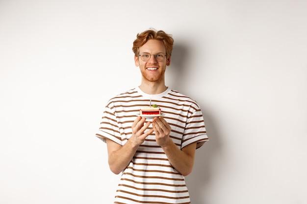 休日とお祝いのコンセプト。キャンドルでバースデーケーキを保持し、笑顔でカメラを見て幸せそうに見える眼鏡のハンサムな赤毛の男。