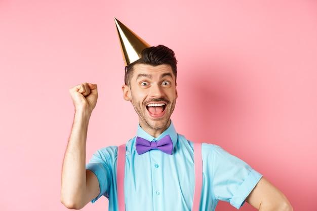 Праздники и концепция празднования. с днем рождения мальчик с усами и галстуком-бабочкой празднует событие в шляпе-конусе и праздничной одежде, поднимает руку и кричит «да».