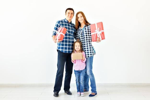 휴일 및 축하 개념 - 크리스마스가 있는 행복한 가족은 복사 공간이 있는 흰색 배경에 선물을 줍니다.